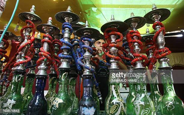 A Palestinian worker makes ready flavoured tobacco water pipes or 'shisha' prior to the evening influx of customers in Gaza City on July 17 as the...