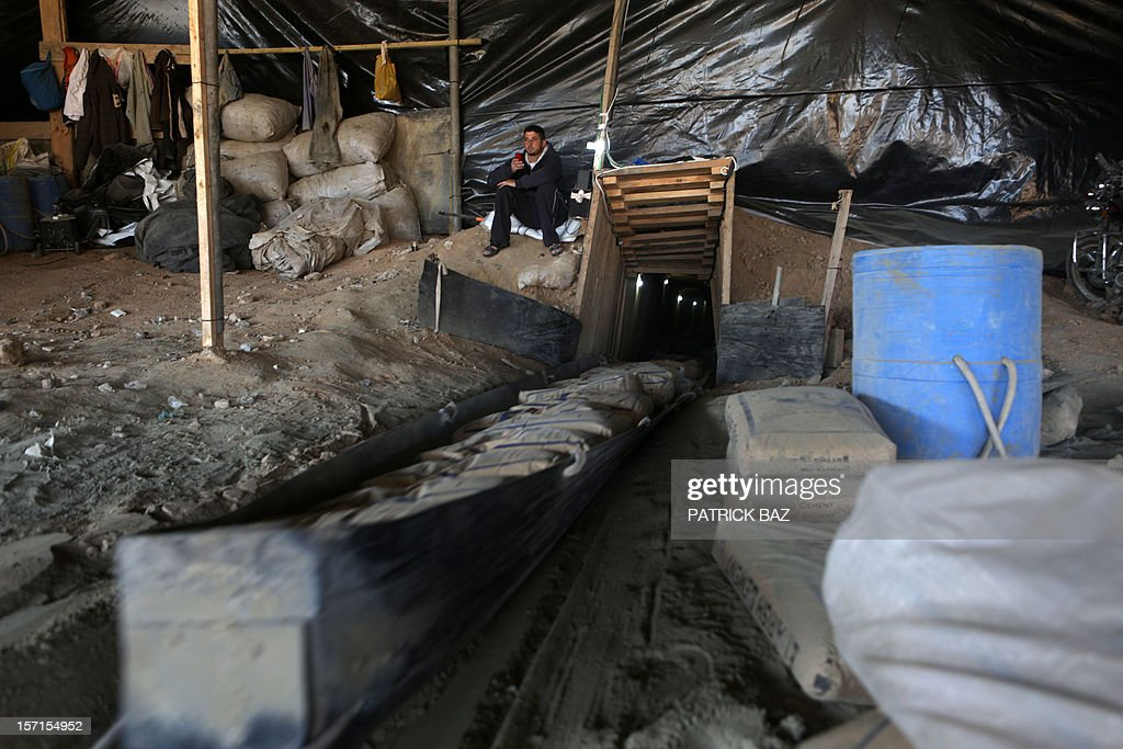 A Palestinian worker monitors a slide loaded with Egyptian cement being pulled from a smuggling tunnel linking the Gaza Strip to Egypt in Rafah on November 29, 2012v. Israeli airforce jets bombed most of the smuggling tunnels in the southern Gaza Strip during its war against the Islamist movement Hamas, which rules the coastal Palestinian territory, between 14 and 21 of November 2012.