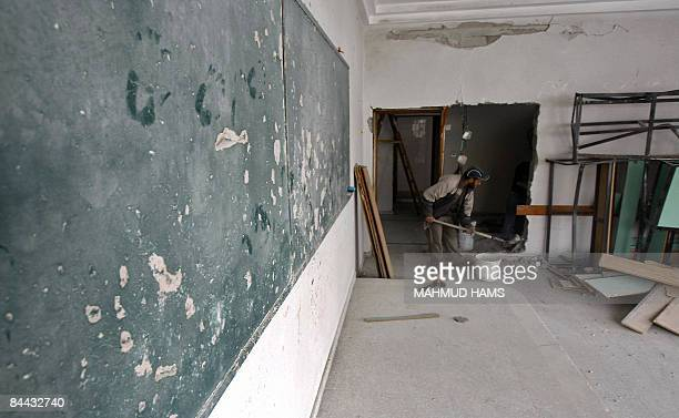 A Palestinian worker repairs a classroom at the Islamic University which was destroyed during Israel's 22day offensive in Gaza City on January 24...