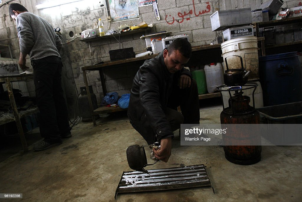 Palestinian worker Shaher alHelou pours melted recycledmetal into a mould at a carbattery workshop March 29 2010 in Jabaliya Gaza Strip Workers at...