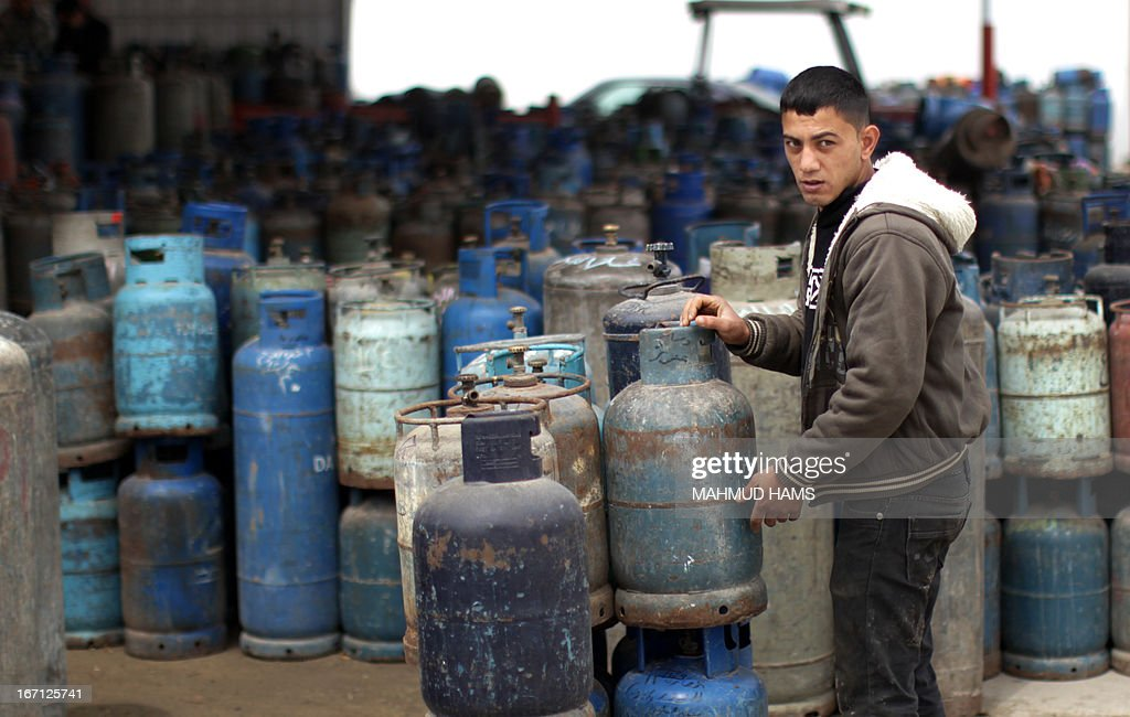 A Palestinian worker shifts empty gas bottles to be refilled at a warehouse in Gaza City on April 21, 2013. The Gaza Strip has been facing a gas crisis for the past two months partially due to the frequent closure of their border crossings by neighboring Israel.