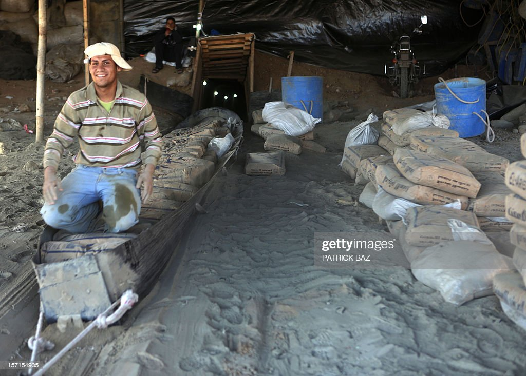 A Palestinian worker sits on a slide loaded with Egyptian cement pulled from a smuggling tunnel linking the Gaza Strip to Egypt, in Rafah, on November 29, 2012. Israeli airforce jets bombed most of the smuggling tunnels in the southern Gaza Strip during its war against the Islamist movement Hamas, which rules the coastal Palestinian territory, between 14 and 21 of November 2012.
