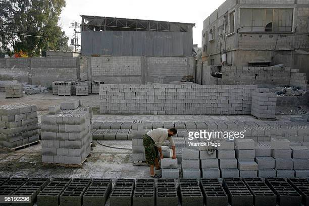 Palestinian worker stacks bricks made with recycled cement gravel and crashed stone at a brick factory March 25 2010 in Khan Younis Gaza Strip In the...