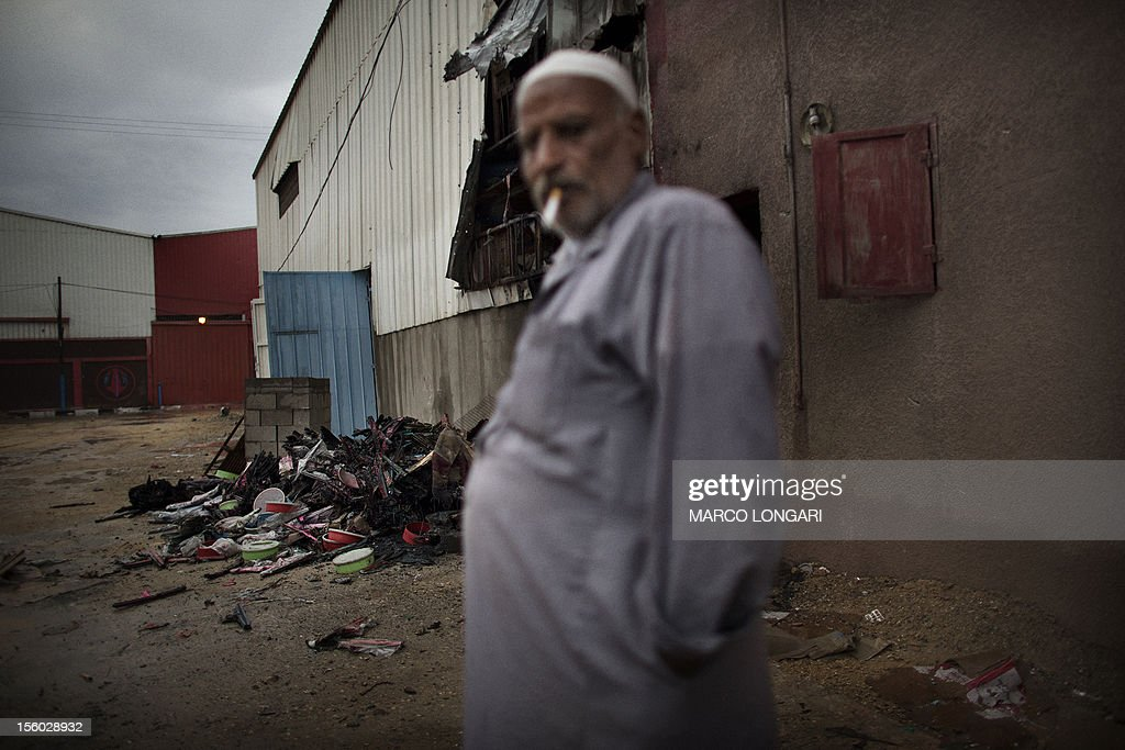 A Palestinian worker stands in front of a damaged plastic factory, in Beit Hanun, in the northern Gaza Strip, on November 11, 2012, following Israeli artillery fire and shelling. Five Gazans were killed and 30 injured by Israeli shelling after militants fired an anti-tank rocket at an Israeli jeep, wounding four soldiers, sources on both sides said.
