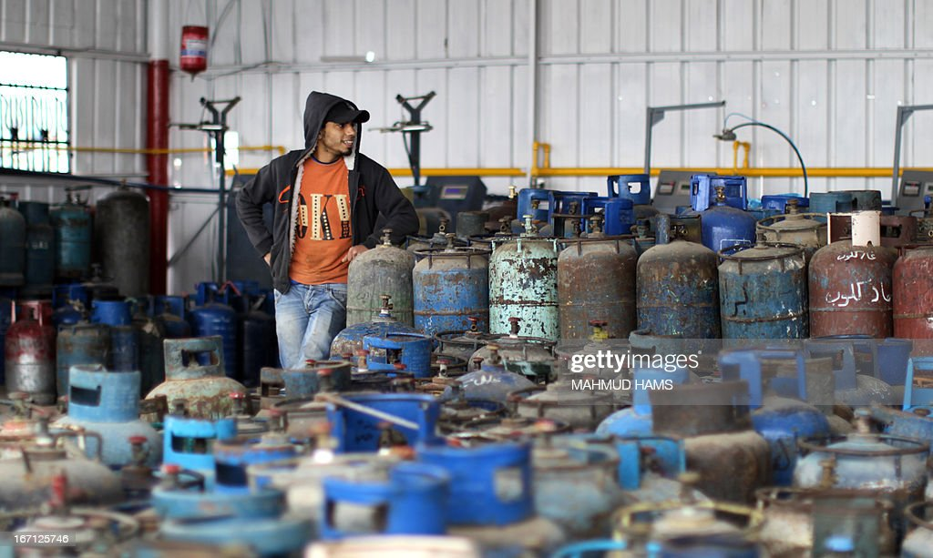 A Palestinian worker stands next to empty gas bottles waiting to be refilled at a warehouse in Gaza City on April 21, 2013. The Gaza Strip has been facing a gas crisis for the past two months partially due to the frequent closure of their border crossings by neighboring Israel.