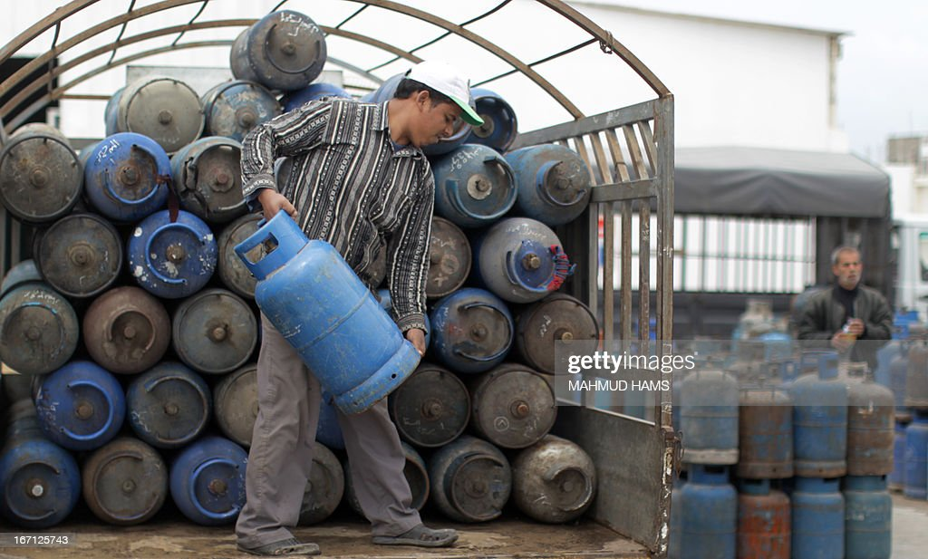 A Palestinian worker unloads empty gas bottles to be refilled at a warehouse in Gaza City on April 21, 2013. The Gaza Strip has been facing a gas crisis for the past two months partially due to the frequent closure of their border crossings by neighboring Israel.