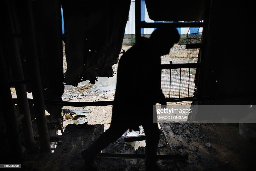 A Palestinian worker walks through a plastic factory that was damaged during Israeli artillery fire and shelling in Beit Hanun, in the northern Gaza Strip, on November 11, 2012. Five Gazans were killed and 30 injured by Israeli shelling after militants fired an anti-tank rocket at an Israeli jeep, wounding four soldiers, sources on both sides said.