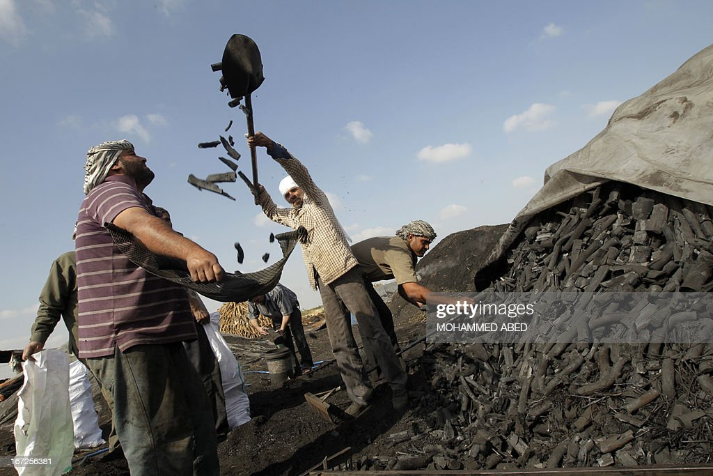 Palestinian workers collect coal at one of the few local charcoal manufacturing plants east of Gaza City on April 23, 2013.
