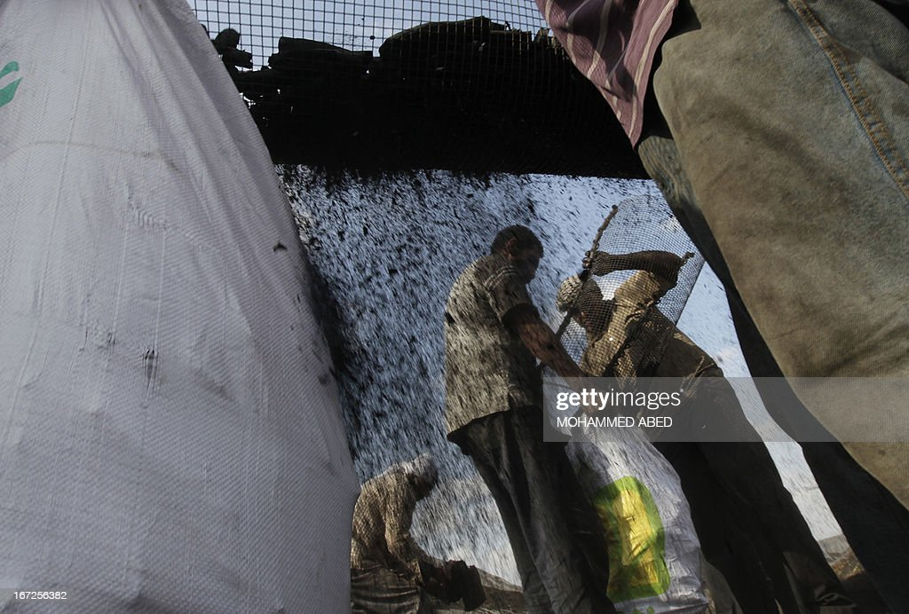 Palestinian workers collect coal at one of the few local charcoal manufacturing plants east of Gaza City on April 23, 2013. AFP PHOTO/MOHAMMED ABED