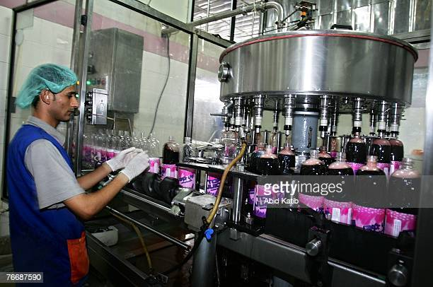 Palestinian workers fill bottles with grape juice on one of five production lines at the Mourtaga soft drink factory on September 12 2007 in Gaza...