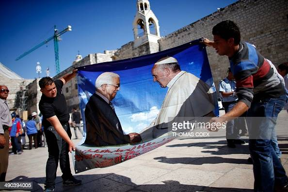 Palestinian workers hold a banner bearing portraits of Palestinian Authority president Mahmud Abbas and Pope Francis in front of the Church of...