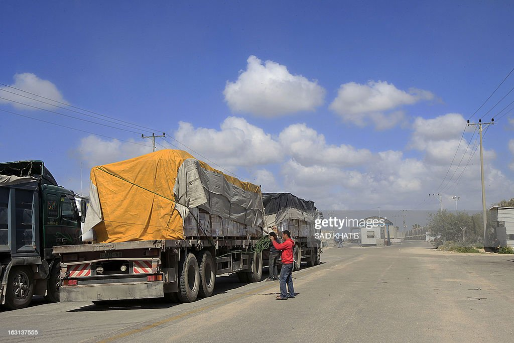 Palestinian workers inspect one of several trucks carrying supplies after it arrived in Rafah town through the Kerem Shalom crossing between Israel and the southern Gaza Strip on March 5, 2013. Israel reopened the Kerem Shalom commercial crossing into southern Gaza, six days after closing it after a rocket fired from the Palestinian enclave hit the Jewish state.