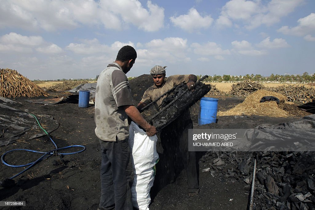 Palestinian workers load coal into a bag at one of the few local charcoal manufacturing plants east of Gaza City on April 23, 2013.