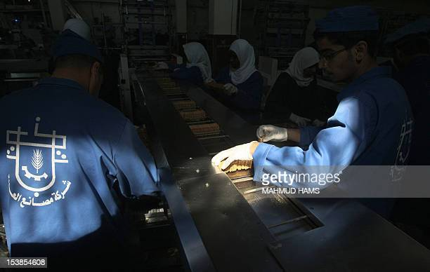 Palestinian workers pack boxes of biscuits at the alAwda factory in Deir alBalah in the central Gaza strip on October 10 2012 The World Food Program...