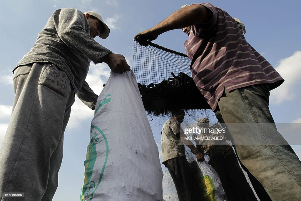 Palestinian workers put coal into bags at one of the few local charcoal manufacturing plants east of Gaza City on April 23, 2013.