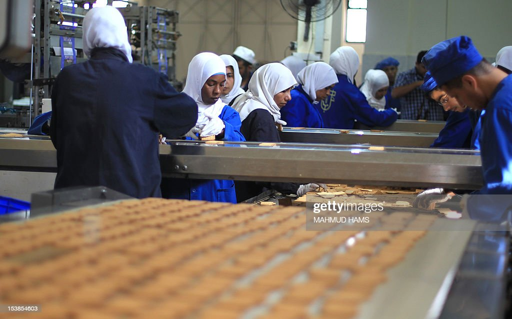 Palestinian workers quality control biscuits at the al-Awda factory in Deir al-Balah, in the central Gaza strip, on October 10, 2012. The World Food Program (WFP) will export the biscuits to United Nation run schools in the Israeli occupied Palestinian West Bank, the first time since 2006 when the Gaza Strip was put under an Israeli blockade. AFP PHOTO / MAHMUD HAMS