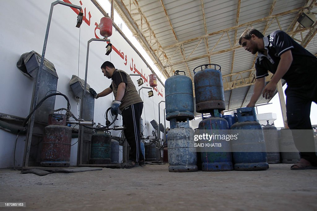 Palestinian workers refill cooking gas bottles at a warehouse in Rafah, in the southern Gaza Strip on November 6, 2013. Palestinian officials said Israel has limited the quantity of cooking gas entering into Gaza, which causes a shortage.