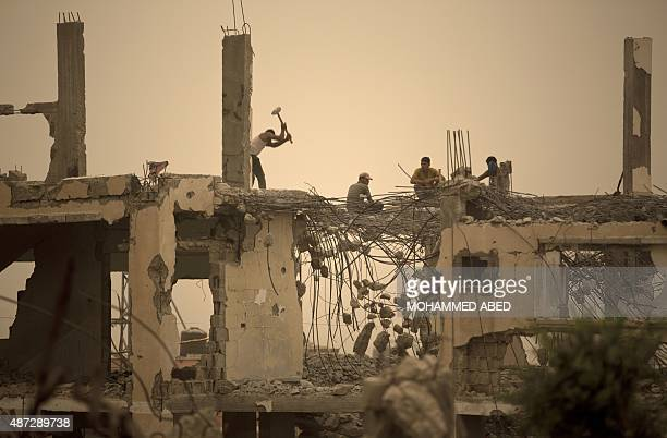 Palestinian workers remove debris from buildings which were destroyed during the 50day war between Israel and Hamas militants in the summer of 2014...