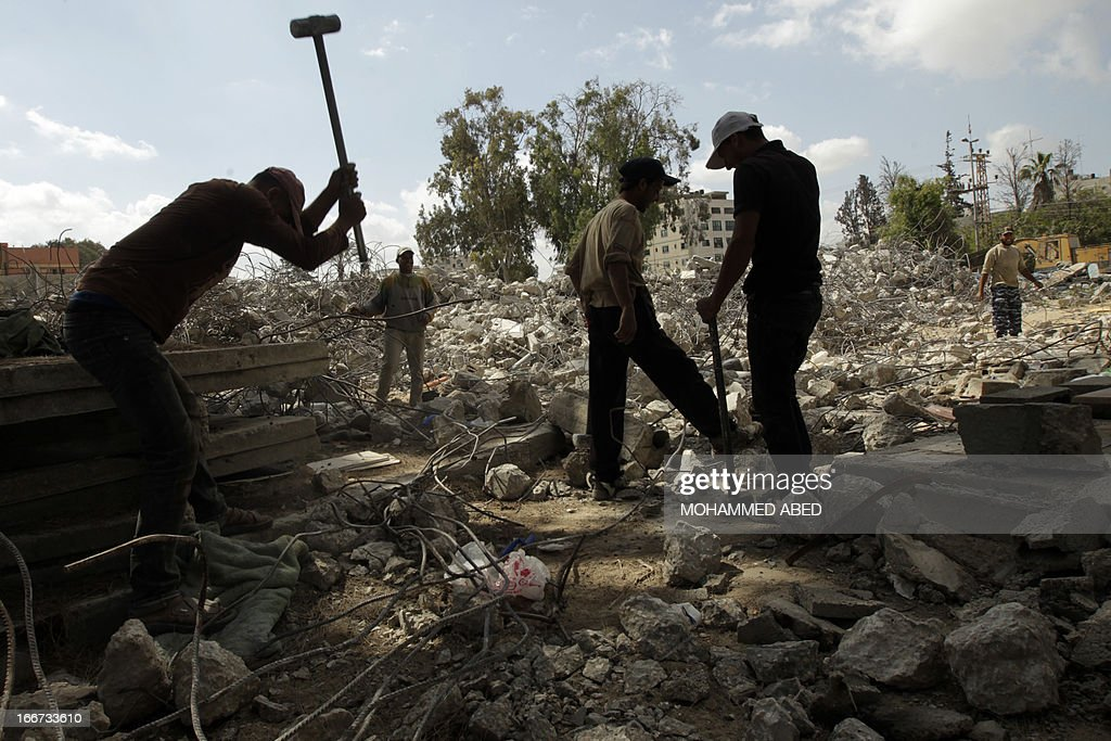 Palestinian workers remove rubble from the ruins of a Hamas security forces headquarters that was destroyed during Israel's last November Gaza campaign, on April 16, 2013 in Gaza City. The eight-day offensive against Gaza Strip militants, codenamed 'Operation Pillar of Defence' by Israel, claimed the lives of 177 Palestinians, including over 100 civilians, and six Israelis, two of them soldiers, according to sources on both sides.