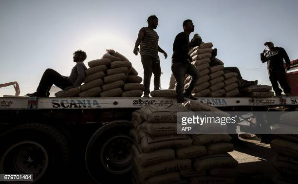 Palestinian workers unload bags of cement from a truck after it entered the southern Gaza Strip from Egypt through the Rafah border crossing after it...