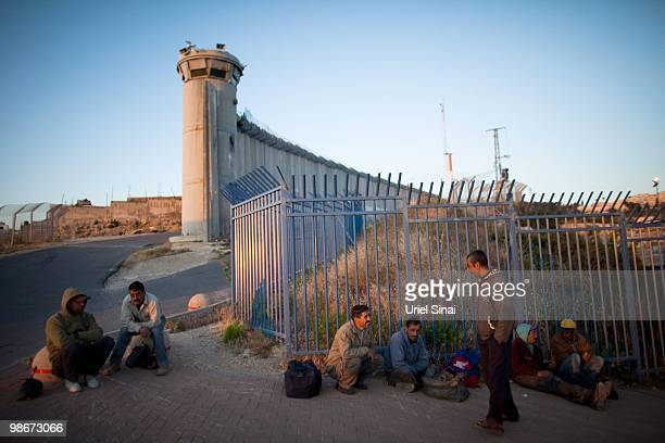 Palestinian workers wait for their employer to collect them after crossing into Israel on April 25 2010 at the Olives Crossing in Al Tur West Bank a...