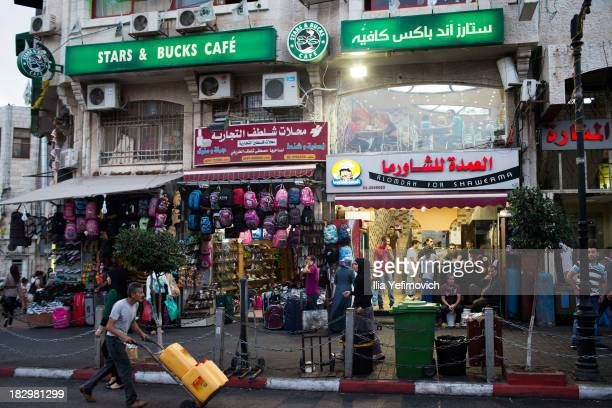 Palestinian workers walk past the Stars and Bucks coffee shop in Manara Square on September 19 2013 in Ramallah WestBank With its name and logo...