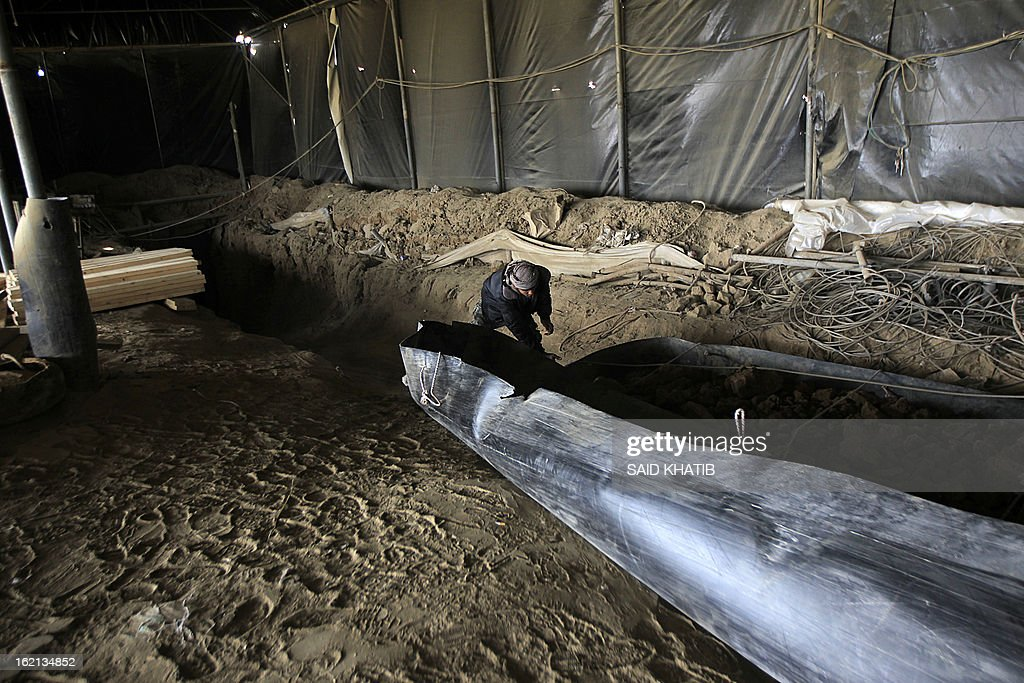 A Palestinian works inside a smuggling tunnel as Egyptian army bulldozer destroy smuggling tunnels along the border with Gaza, in the southern Gaza Strip on February 19, 2013. Gaza's Hamas rulers have closed hundreds of tunnels running under the territory's border with Egypt due to health concerns over some smuggled items, an official said. The tunnels have been a vital lifeline for the flow of goods and fuel into the impoverished territory, which Israel has blockaded since 2006.