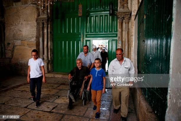 Palestinian worshippers exit through the Chain Gate one of the entrances to Al Aqsa mosque compound in Jerusalem's Old City on July 14 after Israeli...