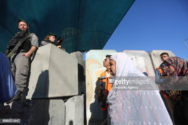 Palestinian worshippers mostly from women wait in a queue from early hours to move for passing through the Qalandiya checkpoint from Ramallah into...