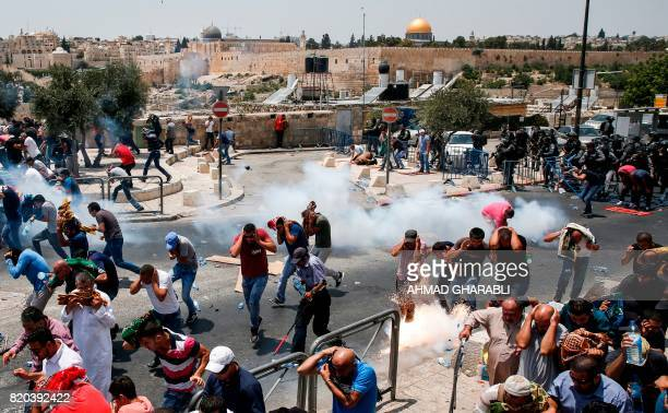 TOPSHOT Palestinian worshippers run for cover from teargas fired by Israeli forces outside Jerusalem's Old City in front of the AlAqsa mosque...