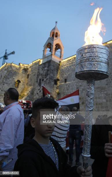 A Palestinian you holds a torch during a gathering in the West Bank town of Bethlehem on April 10 2017 in solidarity with the victims of the twin...