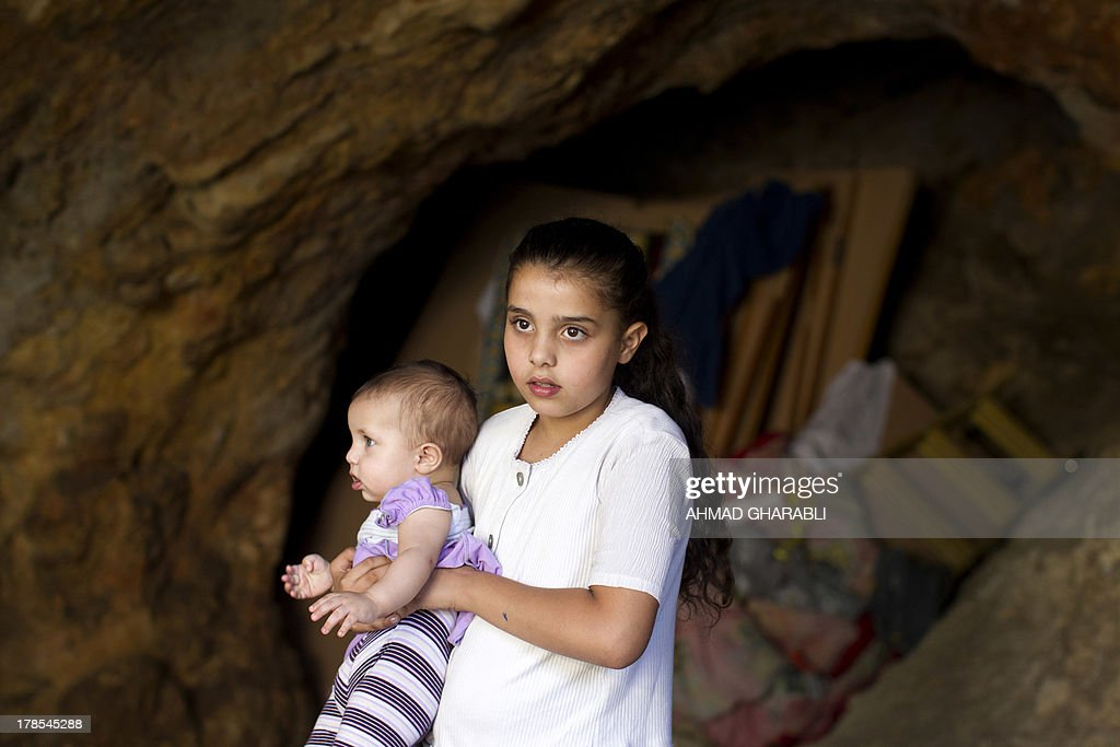 Palestinian young girl holds a baby in the cave that hosts her family since the demolition of their house by Israeli forces on August 29, 2013 in the east Jerusalem neighborhood of Silwan. Israeli forces have destroyed the homes of 716 Palestinians in 2013, according to HRW, which has recorded a three-fold increase in the number of demolitions in east Jerusalem since last year.