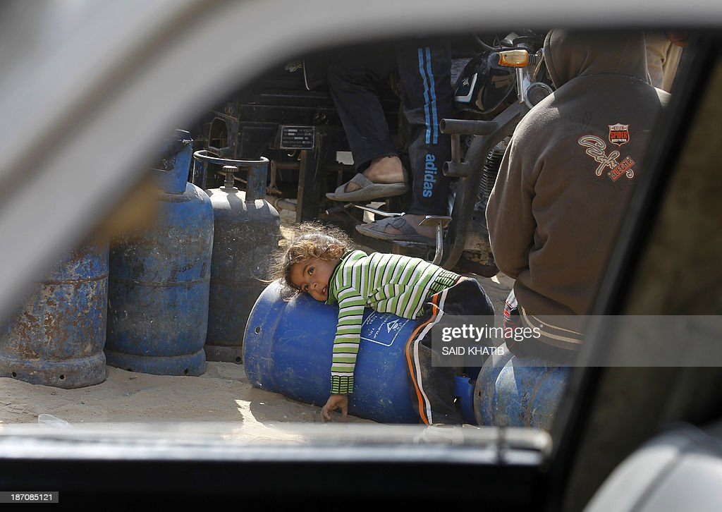 A Palestinian young girl is seen through the window of a car laying on an empty bottle as her family queues to have its cooking gas bottles refilled in Rafah, in the southern Gaza Strip on November 6, 2013. Palestinian officials said Israel has limited the quantity of cooking gas entering into Gaza, which causes a shortage. AFP PHOTO/ SAID KHATIB