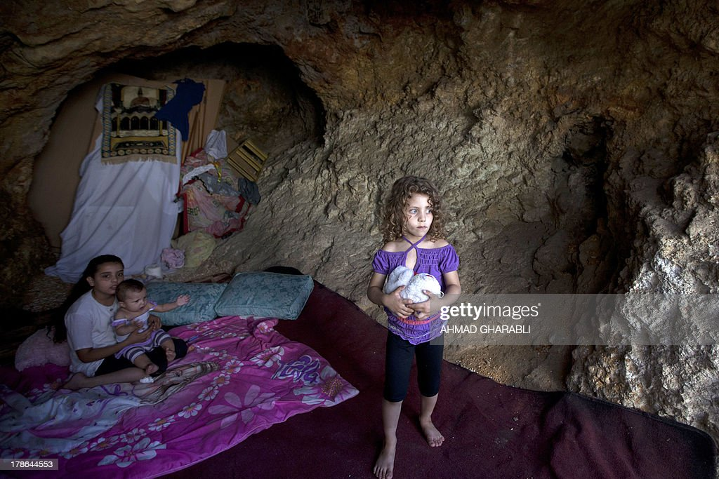 Palestinian young girl stands on a makeshift bed in the cave that hosts her family since the demolition of their house by Israeli forces on August 29, 2013 in the east Jerusalem neighborhood of Silwan. Israeli forces have destroyed the homes of 716 Palestinians in 2013, according to HRW, which has recorded a three-fold increase in the number of demolitions in east Jerusalem since last year.