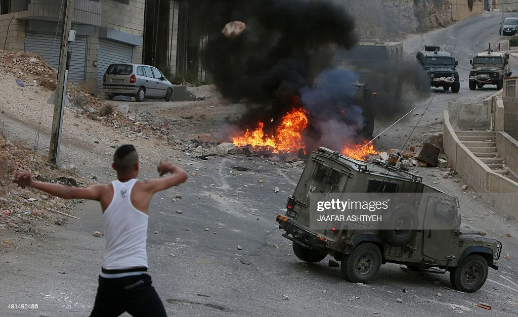 A Palestinian young man throws stones towards vehicles of Israeli security forces who search for the suspected Palestinian killers of a Jewish...