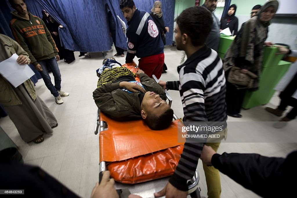 A Palestinian young man, who was wounded during an incident with Israeli forces, arrives on a stretcher at Beit Lahia's hospital, northern Gaza Strip on January 24, 2014. The young man was wounded while Bilal Samir Oweida was 'shot in the chest by Israeli soldiers' east of Jabaliya said Ashraf al-Qudra, a spokesman for the Hamas-run health ministry, as Israeli forces said they had entered 'a prohibited area'. AFP PHOTO/MOHAMMED
