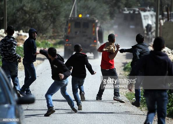 Palestinian young men throw stones towards the vehicles of Israeli soldiers after their inspection following a vandalism attack in alMughayer east of...