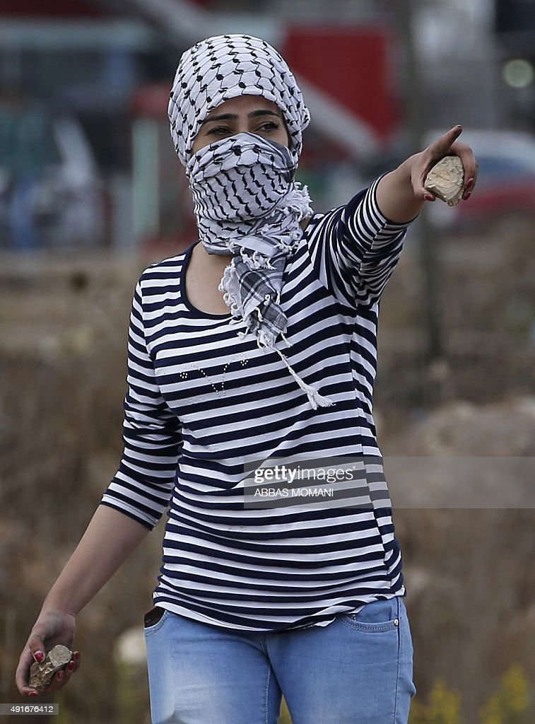 A Palestinian young woman from the Birzeit University holds stones during clashes with Israeli security forces in Beit El on the outskirts of the...