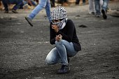 A Palestinian young woman from the Birzeit University looks on during clashes with Israeli security forces in Beit El on the outskirts of the West...
