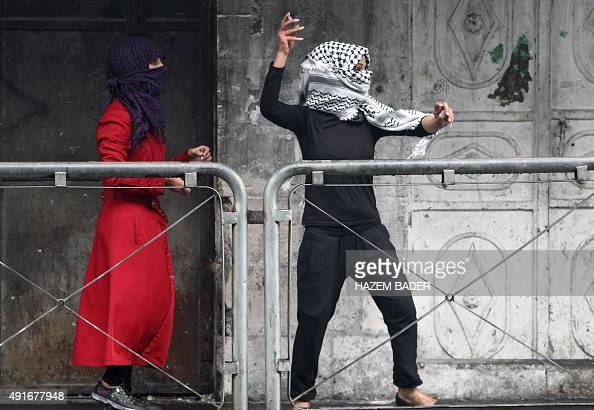 A Palestinian young woman throws stones towards Israeli security forces during clashes in the West Bank town of Hebron on October 7 2015 New violence...