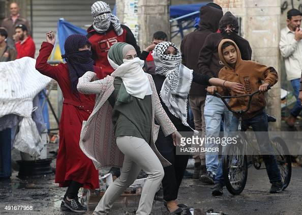 Palestinian young women throw stones towards Israeli security forces during clashes in the West Bank town of Hebron on October 7 2015 New violence...