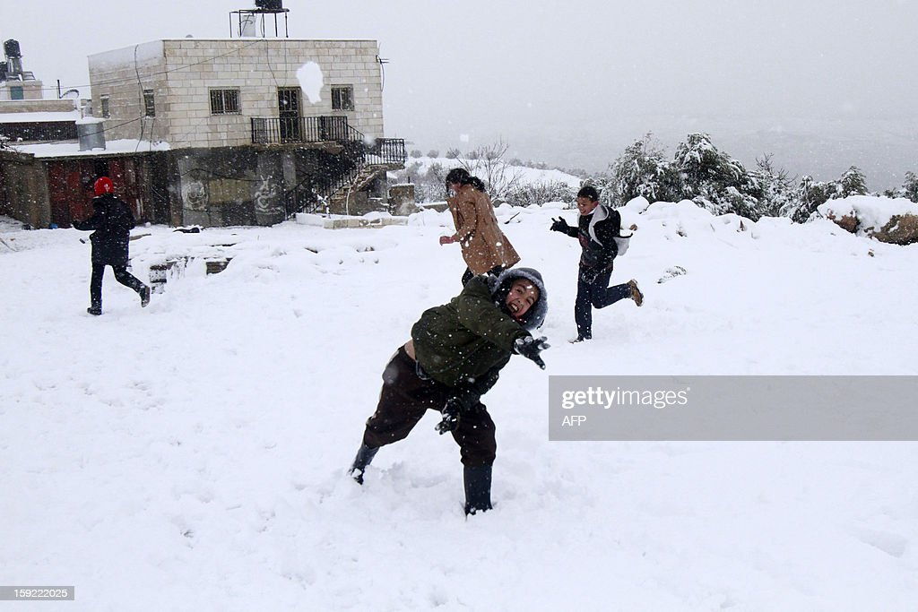 Palestinian youngs play with snow balls after heavy snow falls on January 10, 2013 in Tuqua, near the West Bank City of Bethlehem. Abnormal storms, which for four days have blasted the Middle East with rain, snow and hail, leave swathes of Israel and Jordan under a blanket of snow and parts of Lebanon blacked out.