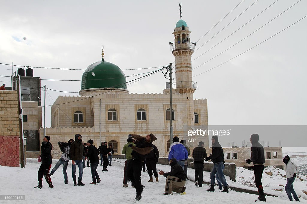 Palestinian youngs play with snow balls in front of a mosque after heavy snow falls on January 10, 2013 in Tuqua, near the West Bank City of Bethlehem. Abnormal storms, which for four days have blasted the Middle East with rain, snow and hail, leave swathes of Israel and Jordan under a blanket of snow and parts of Lebanon blacked out.