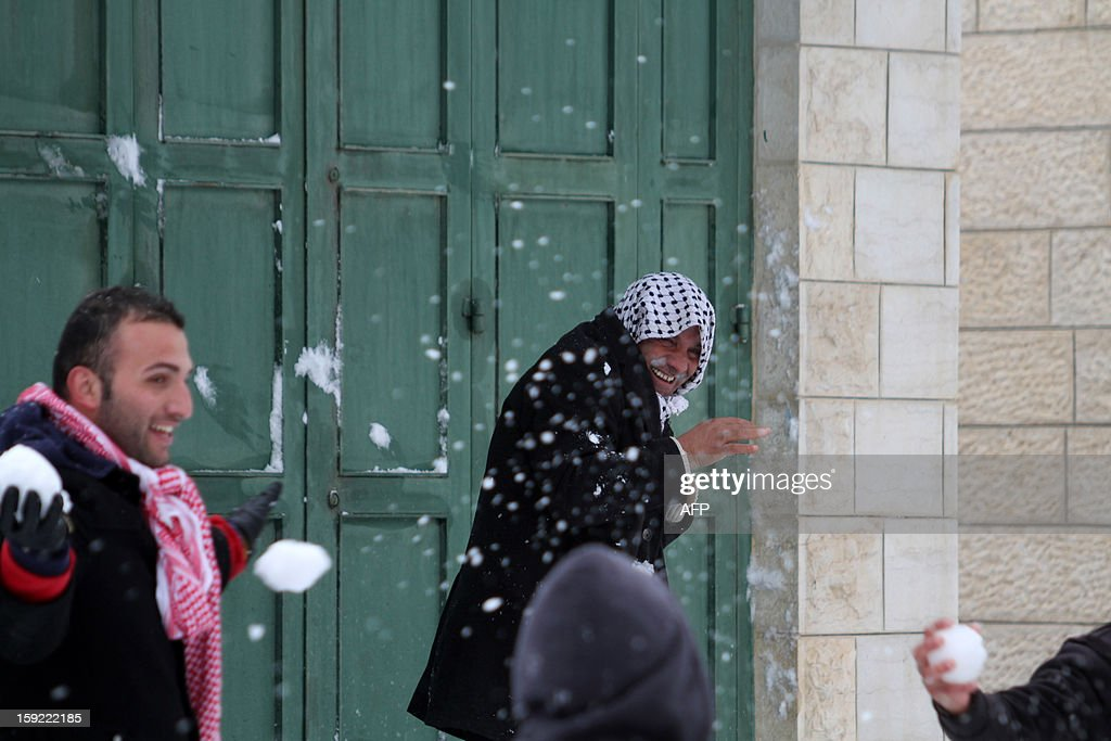 Palestinian youngs play with snow balls in front of an elderly man smiling after heavy snow falls on January 10, 2013 in Tuqua, near the West Bank City of Bethlehem. Abnormal storms, which for four days have blasted the Middle East with rain, snow and hail, leave swathes of Israel and Jordan under a blanket of snow and parts of Lebanon blacked out. AFP PHOTO/MUSA AL SHAER