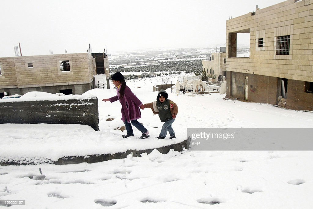 Palestinian youngs walk on a snow-covered street after heavy snow falls on January 10, 2013 in Tuqua, near the West Bank City of Bethlehem. Abnormal storms, which for four days have blasted the Middle East with rain, snow and hail, leave swathes of Israel and Jordan under a blanket of snow and parts of Lebanon blacked out. AFP PHOTO/MUSA AL SHAER