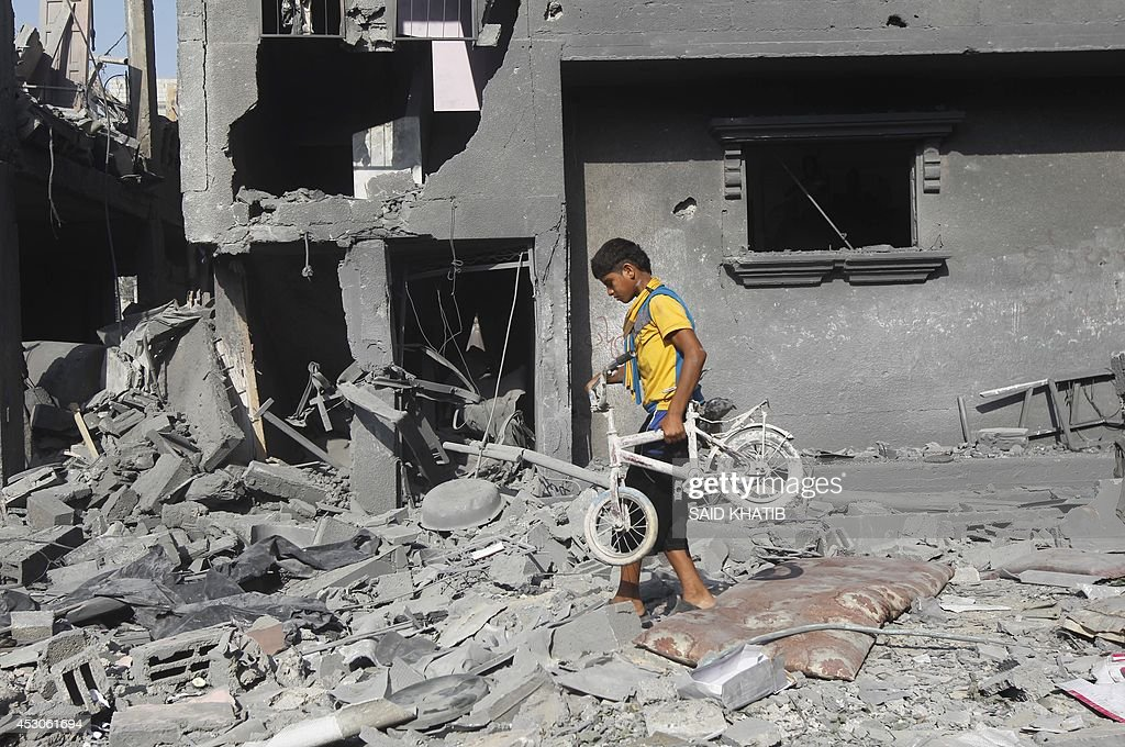 A Palestinian youth carries a bicycle from the wreckage of a building which was hit in an Israeli strike in Rafah in the southern Gaza Strip on...