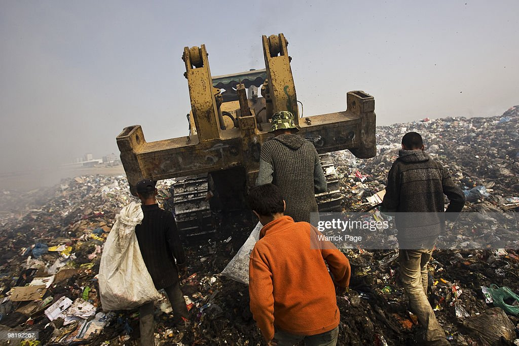 Palestinian youth collect plastic to be sold for recycling from a landfill March 23 2010 at the Gaza and Israel border Hamas' Ministry of Economics...