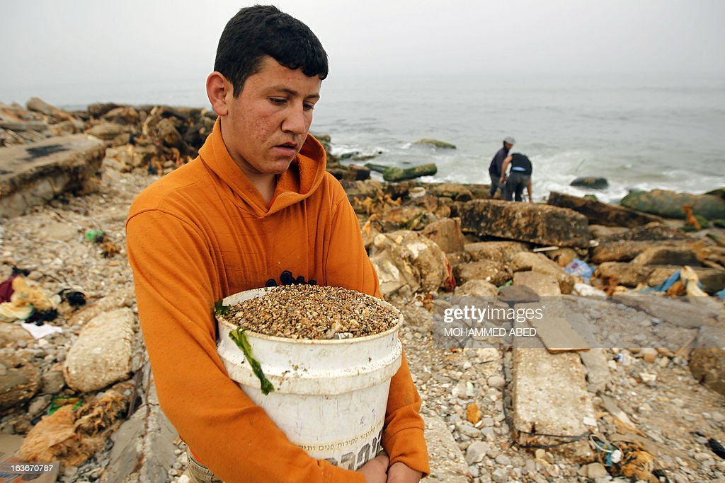 A Palestinian youth collects small pebbles from the beach for use in construction work and decorating houses in Gaza City on March 14, 2013. AFP PHOTO/MOHAMMED ABED