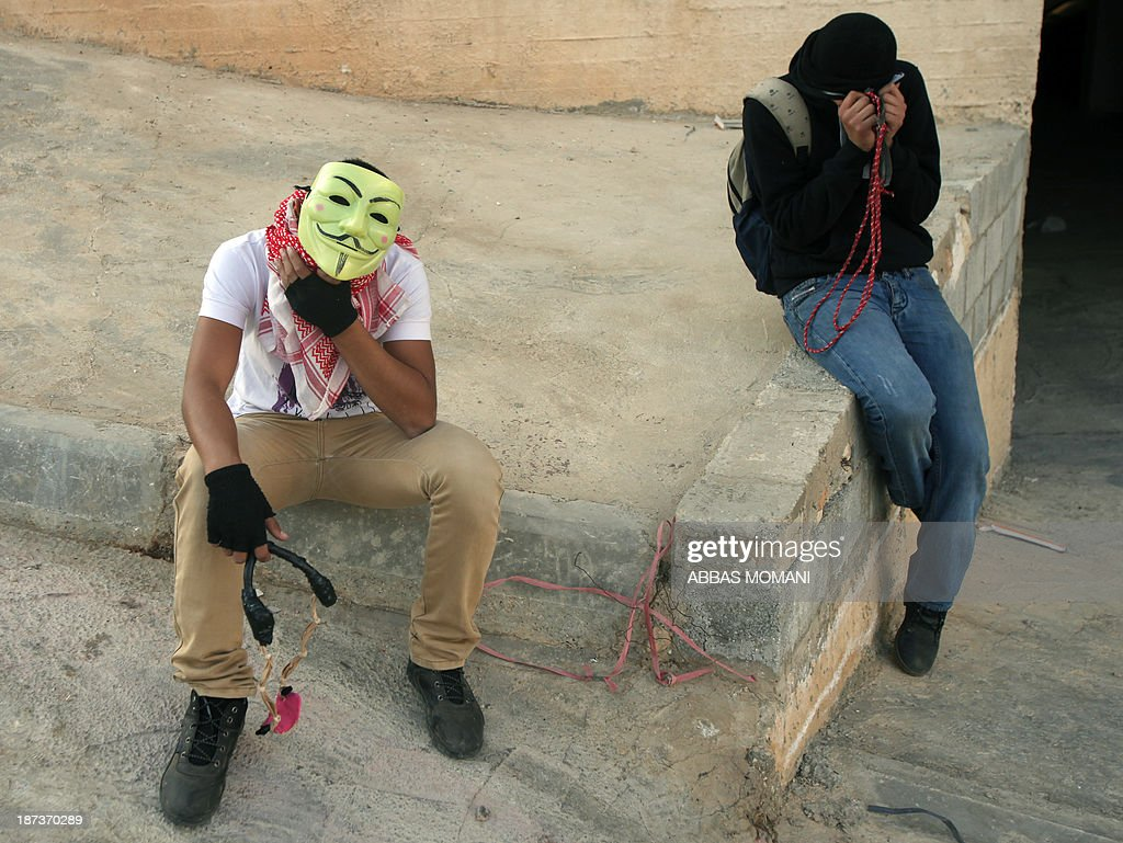Palestinian youth cover their eyes after being caught in tear gas during clashes with Israeli soldiers close to the Israeli Ofer military prison, near the West Bank village of Betunia, on November 8, 2013. The clashes errupted a day after Israeli forces killed a Palestinian near Jerusalem, Israeli police and family members said, as the United States warned of a third intifada if Middle East peace talks fail. AFP PHOTO/ABBAS MOMANI