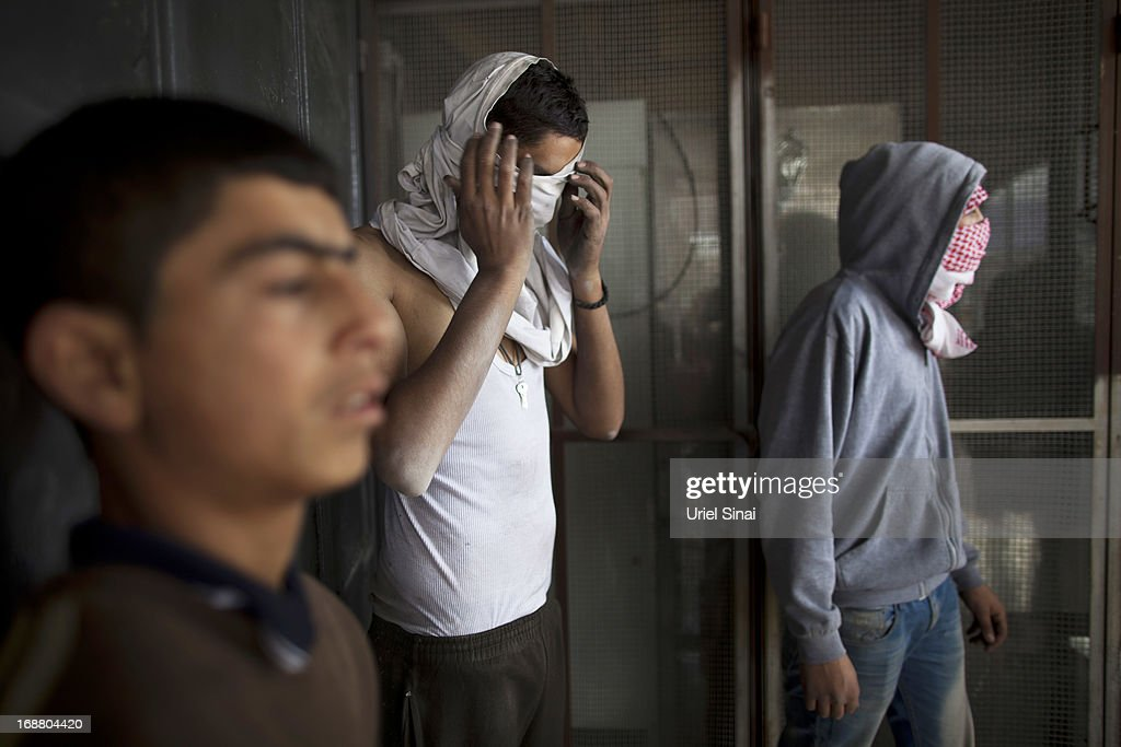 A Palestinian youth covers his face during clashes with the Israeli army during Nakba day on May 15, 2013 near the Qalandia checkpoint at the outskirts of Ramallah, the West Bank. Palestinians mark Israel's establishment in 1948 with 'Nakba' or 'catastrophe' day on May 15, to remember the thousands of Palestinians who fled or were expelled during the creation of the Jewish state and the subsequent war.